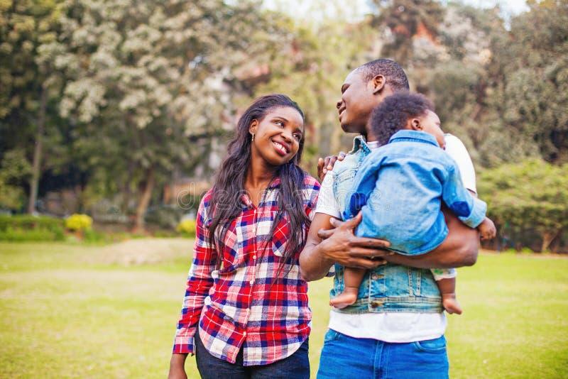 Familia africana que camina en el parque fotos de archivo