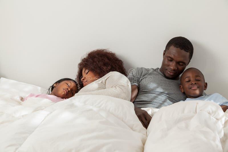 Familia africana que duerme en la cama junto fotografía de archivo