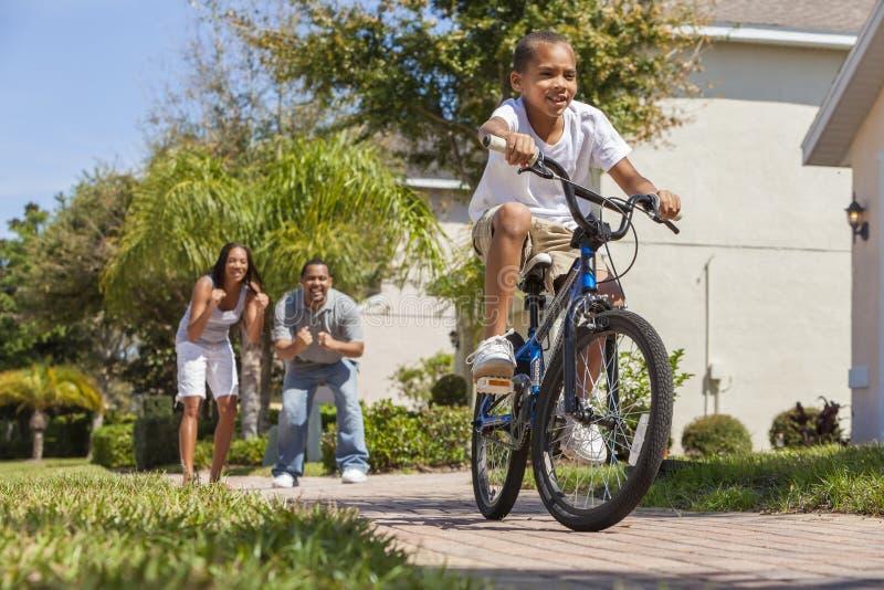 Familia afroamericana con la bici del montar a caballo del muchacho y padres felices foto de archivo