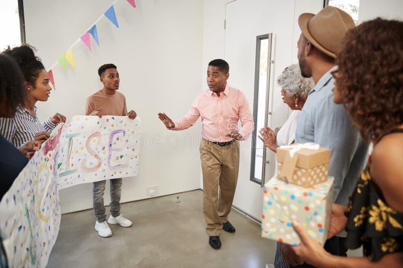 Familia afroamericana de tres generaciones que se prepara para hacer una recepción del partido de sorpresa, integral foto de archivo