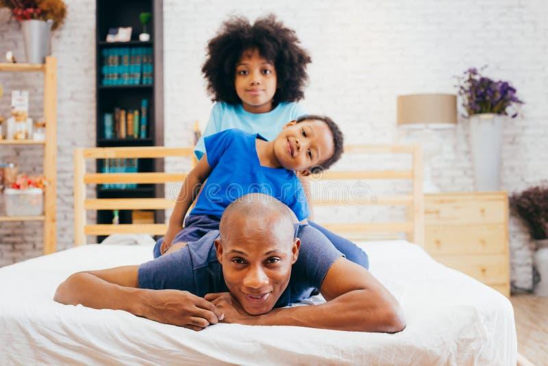 Familia afroamericana de tres, niños que se sientan en la parte posterior del ` s del padre foto de archivo