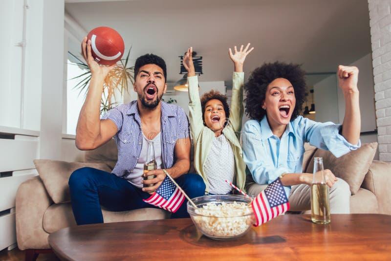 Familia afroamericana de tres TV de observación y juegos del deporte que animan en el sofá en casa imágenes de archivo libres de regalías