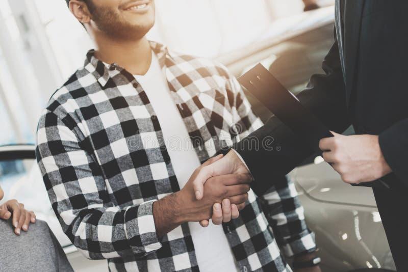 Familia afroamericana en la concesión de coche Vendedor y hombre que sacuden las manos, felicitando con el nuevo coche imagen de archivo