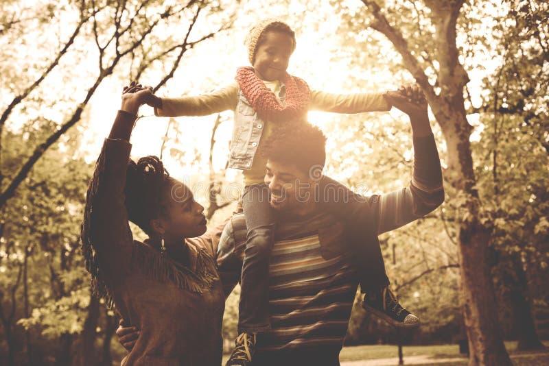 Familia afroamericana joven en parque junto fotografía de archivo