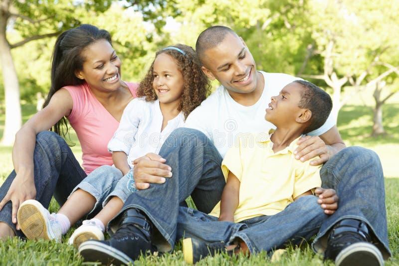 Familia afroamericana joven que se relaja en parque imagen de archivo