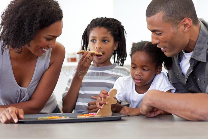 Familia afroamericana que come las galletas hechas en casa imagen de archivo libre de regalías
