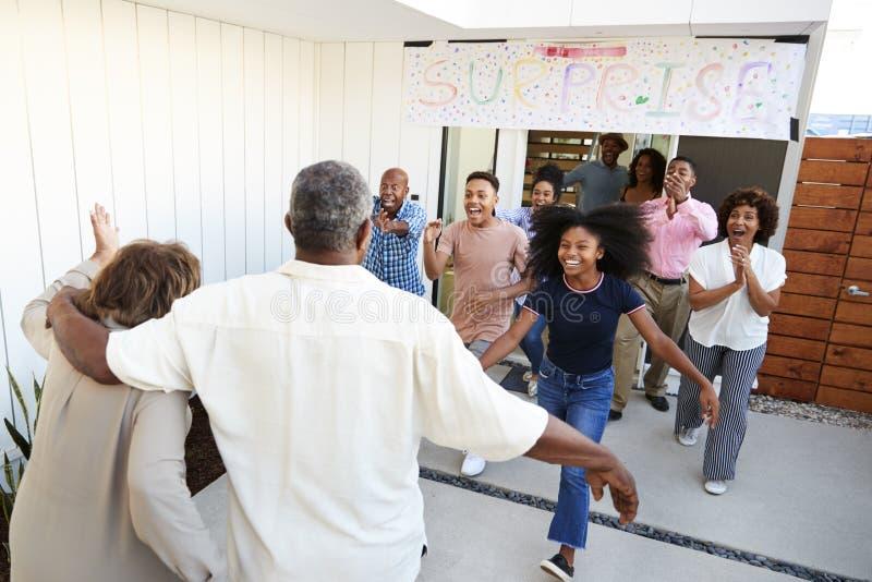 Familia afroamericana que corre para acoger con satisfacción a los abuelos para un partido de la familia de la sorpresa fotos de archivo libres de regalías