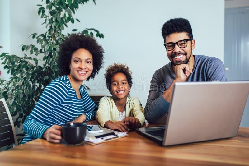 Familia afroamericana usando el ordenador port?til en la sala de estar imagen de archivo