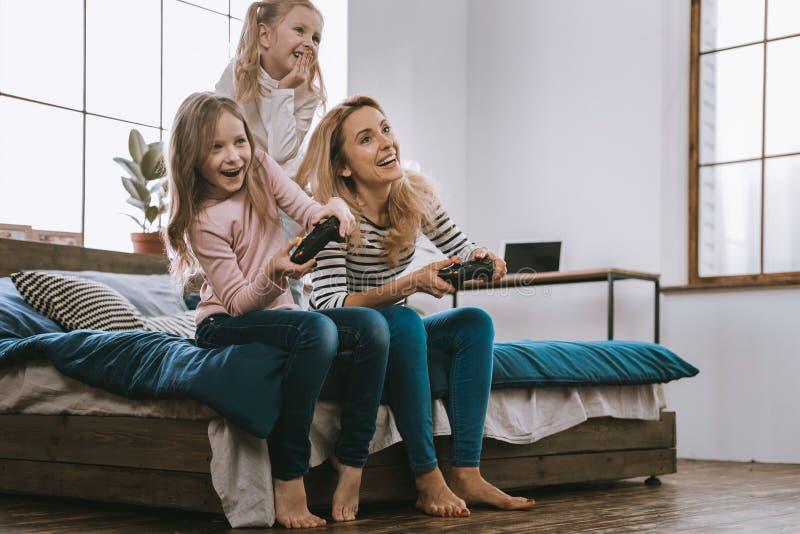 Familia agradable alegre que juega a los videojuegos imagenes de archivo