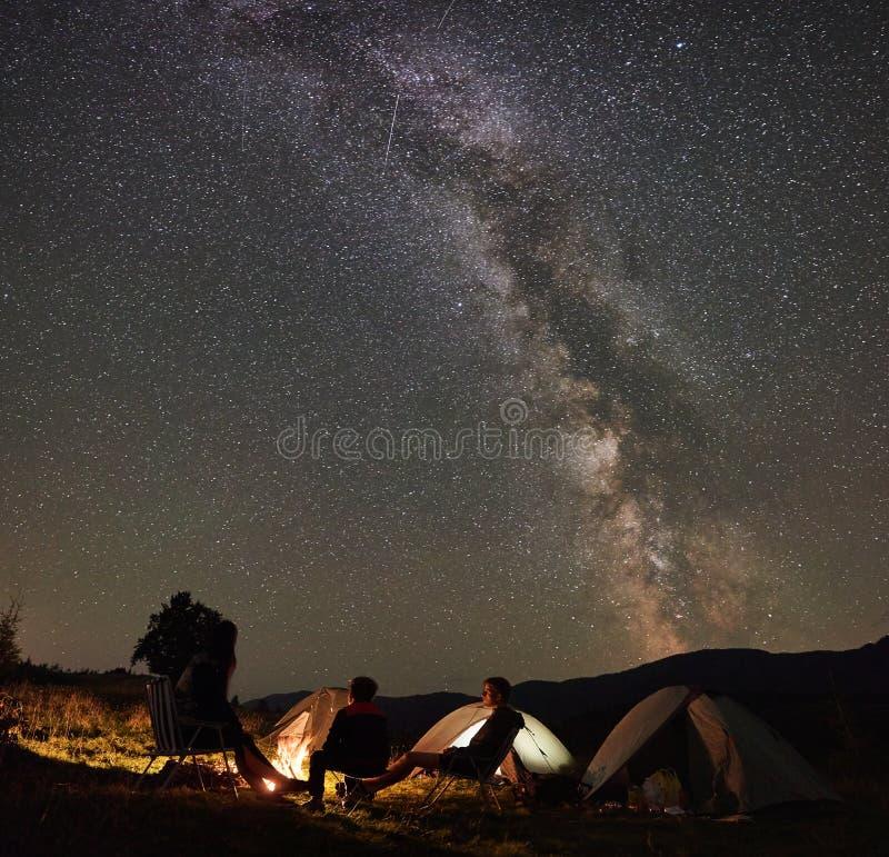 Familia al lado del campo, hoguera, tienda debajo del cielo estrellado de la noche fotografía de archivo libre de regalías