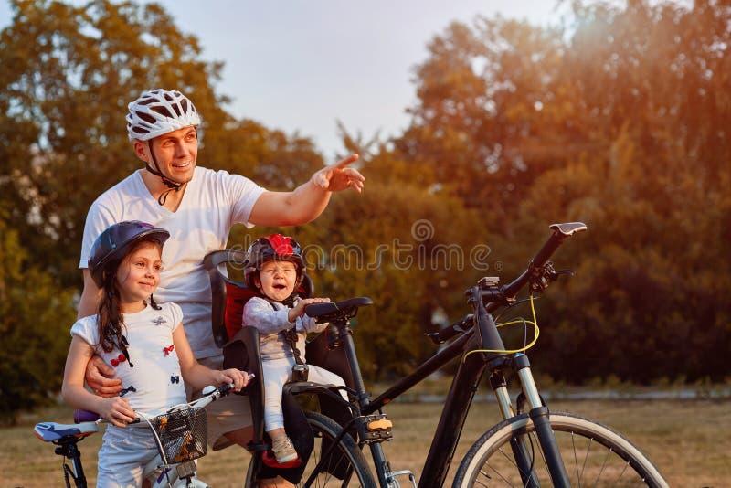 Familia alegre biking en parque imagenes de archivo