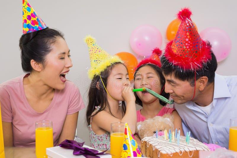 Familia alegre con la torta y los regalos en una fiesta de cumpleaños imagen de archivo
