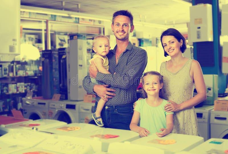Familia alegre con las mercancías que hacen compras de los niños en hogar imágenes de archivo libres de regalías