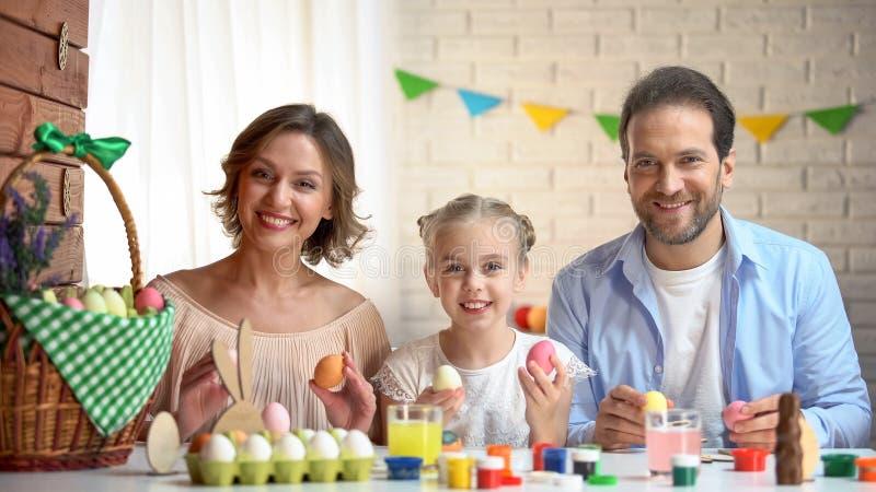Familia alegre con los huevos de Pascua que miran la cámara, actividad tradicional, día de fiesta fotos de archivo libres de regalías