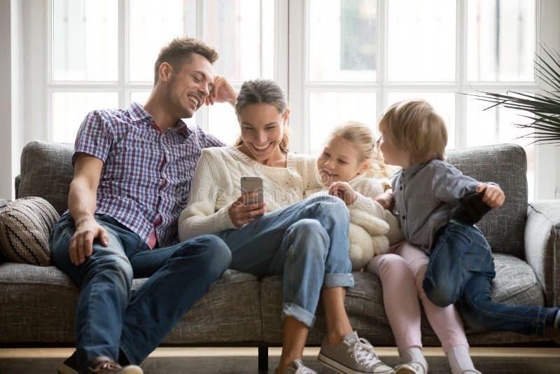 Familia alegre con los niños que ríen el vídeo divertido de observación en elegante fotografía de archivo