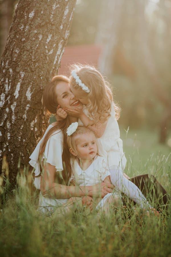 Familia alegre en un parque, mam? y su hija preciosa dos a sentarse en la hierba mientras que est?n mirando la c?mara fotografía de archivo