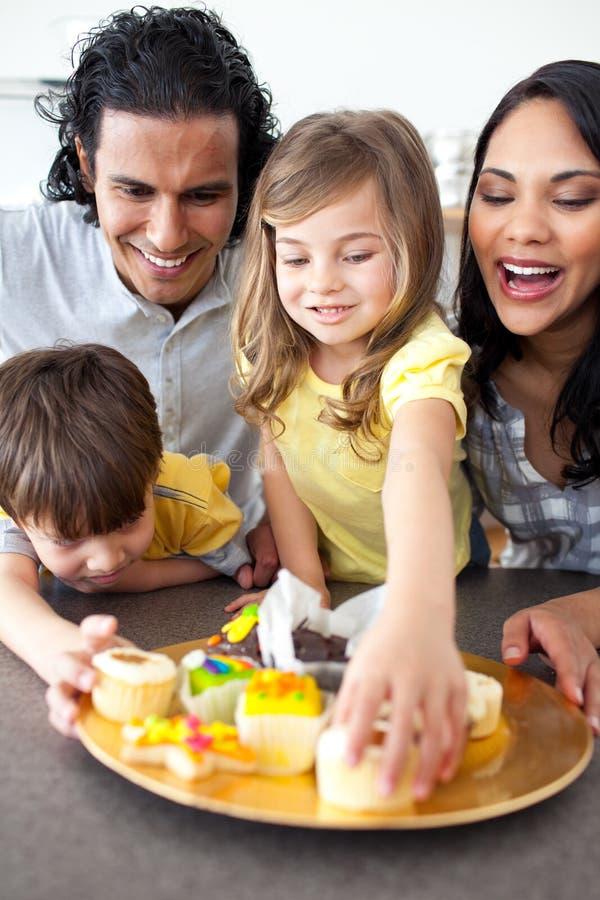 Familia alegre que come las galletas fotos de archivo