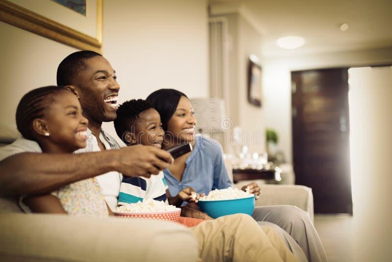 Familia alegre que come palomitas mientras que mira la televisión fotos de archivo