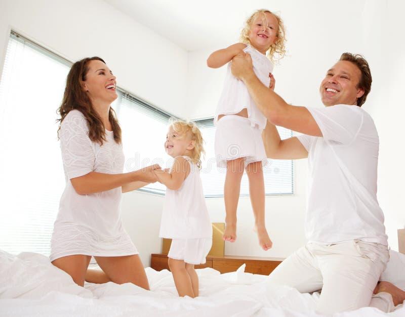 Familia alegre que juega en el dormitorio imágenes de archivo libres de regalías