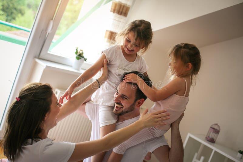 Familia alegre que juega junto en cama foto de archivo