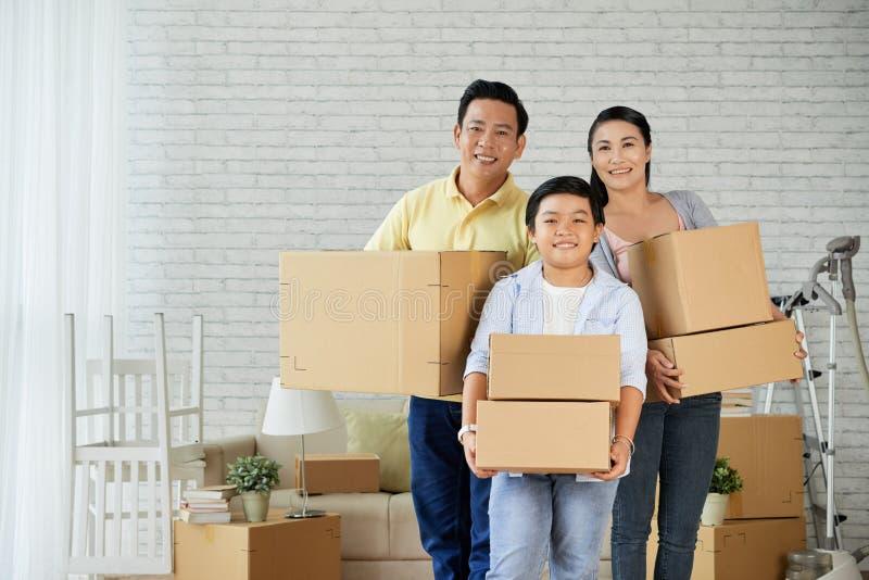 Familia alegre que se mueve en el nuevo apartamento imagen de archivo