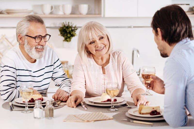Familia alegre que se sienta en la tabla de cena en la cocina fotos de archivo