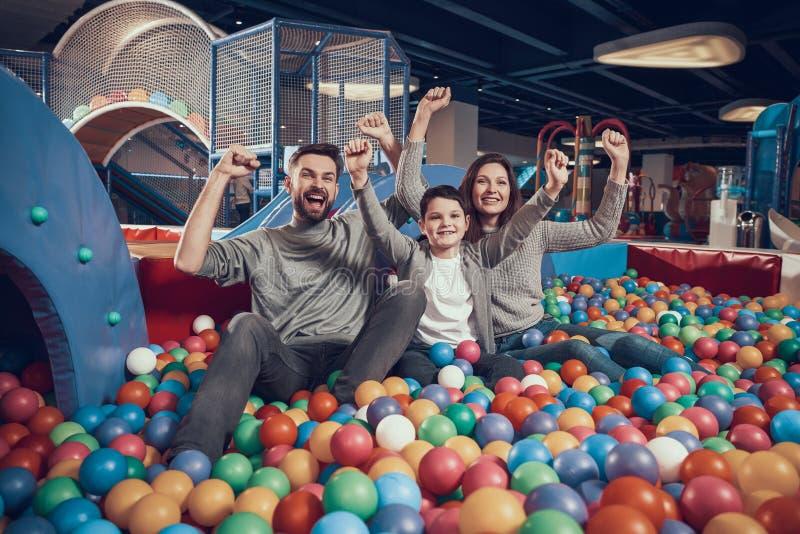 Familia alegre que se sienta en piscina con las bolas fotografía de archivo