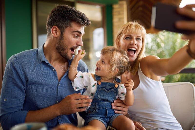 Familia alegre que toma la foto en terraza fotografía de archivo