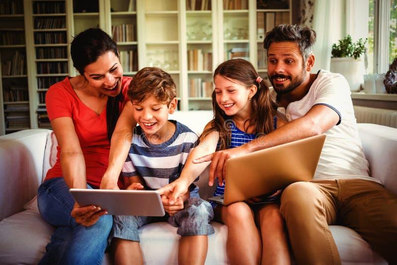 Familia alegre usando tecnologías mientras que se sienta en el sofá imágenes de archivo libres de regalías