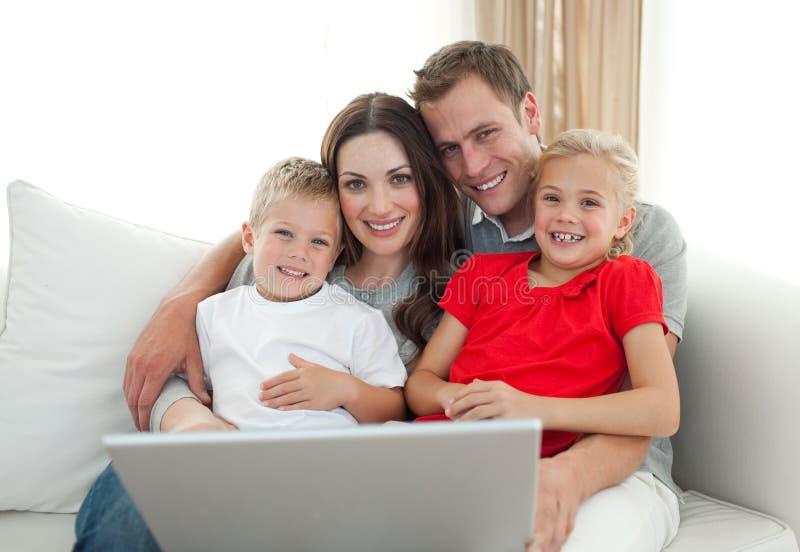 Familia alegre usando un ordenador que se sienta en el sofá imágenes de archivo libres de regalías