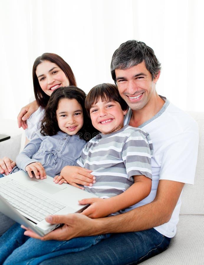 Familia alegre usando una computadora portátil que se sienta en el sofá imagenes de archivo