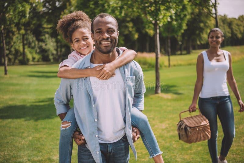 Familia americana afican feliz en parque fotografía de archivo libre de regalías