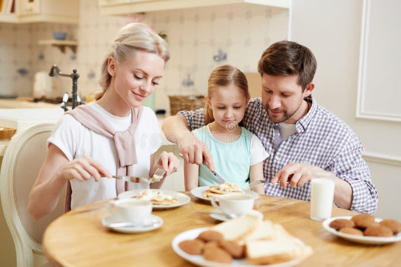 Familia amistosa feliz que come el desayuno por mañana imagenes de archivo