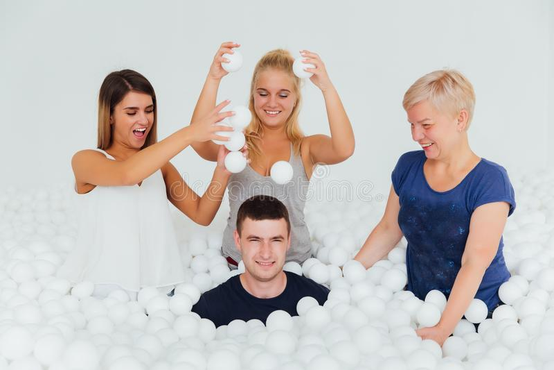 Familia amistosa feliz rodeada por las bolas plásticas blancas en la piscina seca fotos de archivo