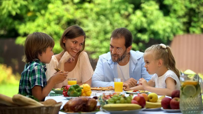 Familia amistosa que tiene aire libre tradicional de la cena, niños de los padres felices junto imagen de archivo