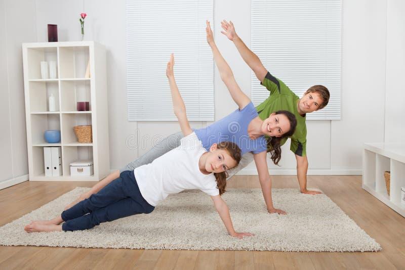 Familia apta que hace yoga lateral del tablón en casa imágenes de archivo libres de regalías