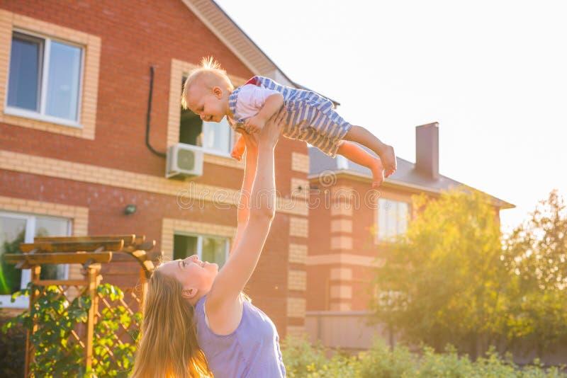 Familia armoniosa feliz al aire libre la madre lanza al bebé para arriba, riendo y jugando en el verano en la naturaleza imagenes de archivo