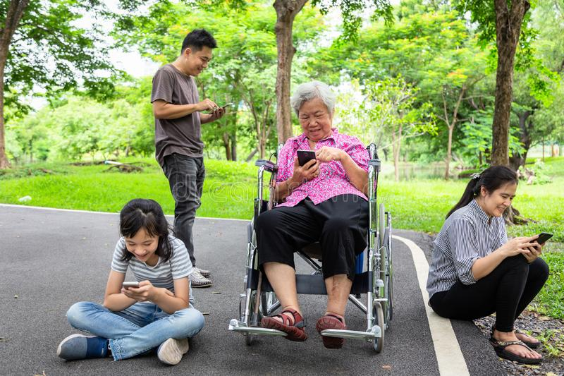 Familia asiática, abuela mayor, padre, madre, hija con Internet, adicto al teléfono móvil, muchacha del niño que juega al videoju foto de archivo libre de regalías