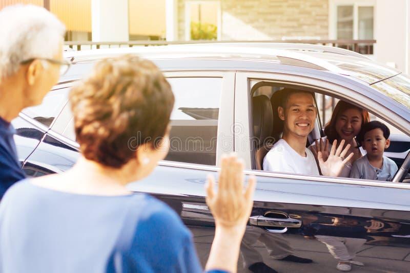 Familia asiática de padre, madre e hijo que agitan adiós al abuelo y a la abuela como sacan su viaje imágenes de archivo libres de regalías