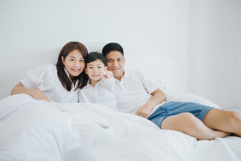 Familia asiática feliz con el hijo en casa en jugar del dormitorio y l fotos de archivo libres de regalías