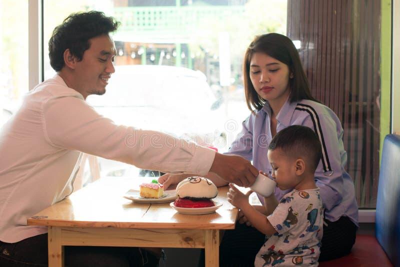 Familia asi?tica feliz, con un todler pasando el tiempo junto dentro de tienda y del caf? de la panader?a comiendo la torta imagen de archivo libre de regalías