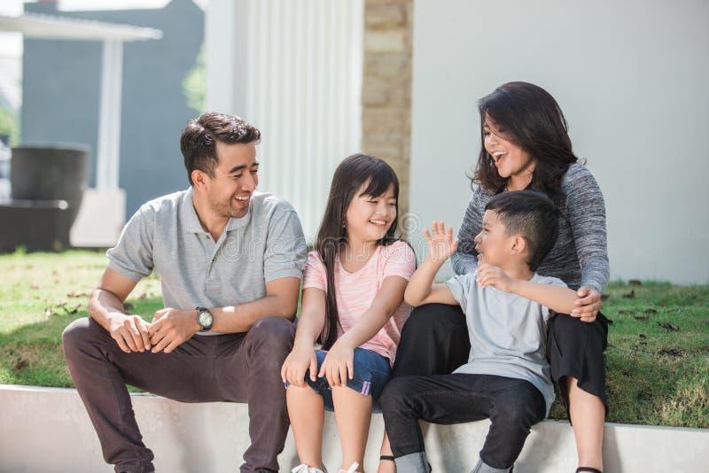 Familia asiática feliz delante de su casa imagenes de archivo
