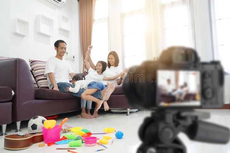 Familia asiática feliz en sala de estar en casa, con la grabación haciendo el vídeo foto de archivo libre de regalías
