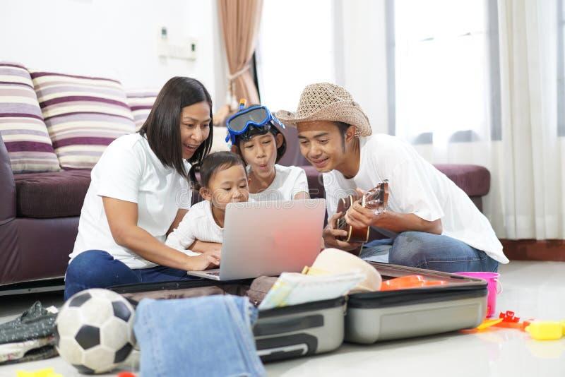 Familia asiática feliz en un piso en casa que planea el viaje t de las vacaciones fotos de archivo libres de regalías