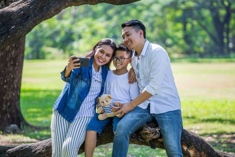 familia asiática feliz, padres y sus niños tomando el selfie en parque junto padre, madre, hijo que se sienta en rama del árbol g foto de archivo