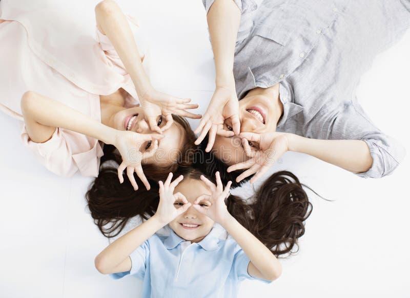Familia asiática feliz que miente en el piso imagen de archivo
