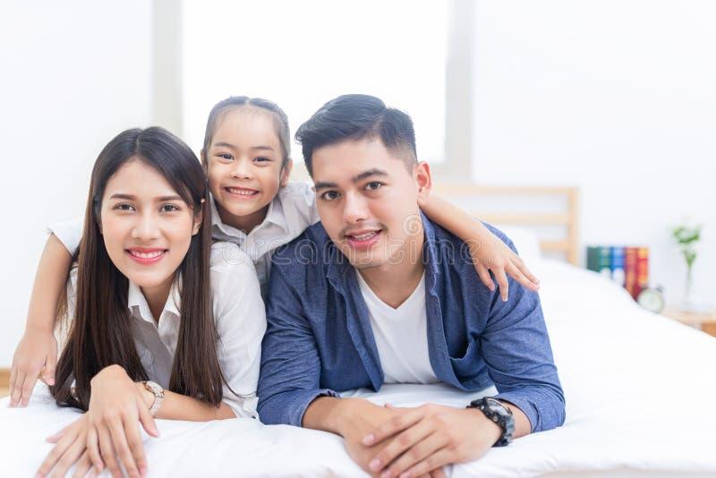 Familia asiática feliz que miente en una cama fotos de archivo