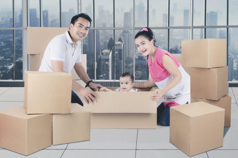 Familia asiática joven que se divierte que desempaqueta las cajas foto de archivo libre de regalías