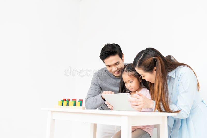 Familia asiática preciosa joven, padres y pequeño niño usando la tableta digital en casa con el espacio de la copia Hija de enseñ fotos de archivo