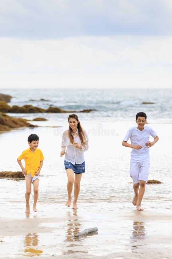 Familia asiática que corre en la playa de la arena en día nublado fotos de archivo